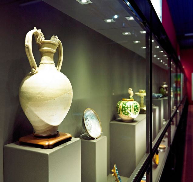 Various items of pottery on display in a glass cabinet