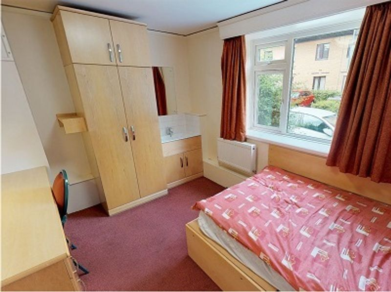 Student bedroom with a single bed, wardrobe, cupboards and desk