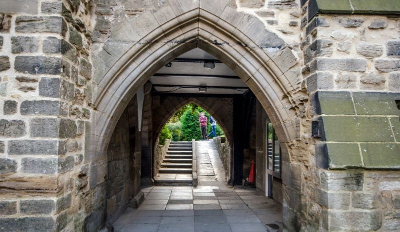 The college grounds chapel archway, people stand talking on the other side