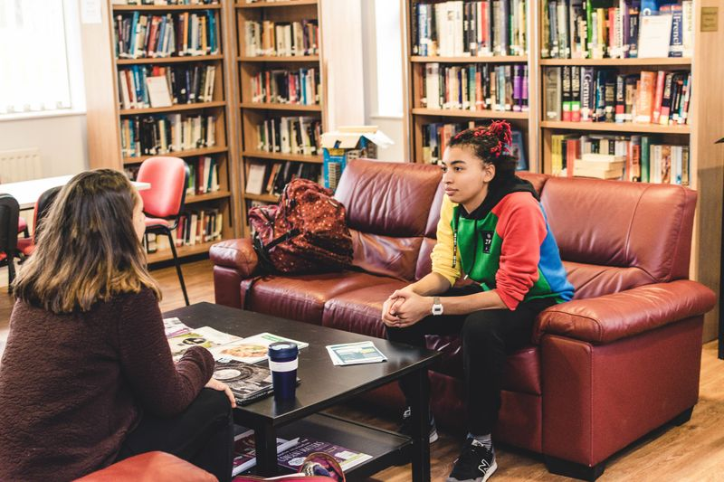 Students sat on sofas surrounded by book shelves in the common room