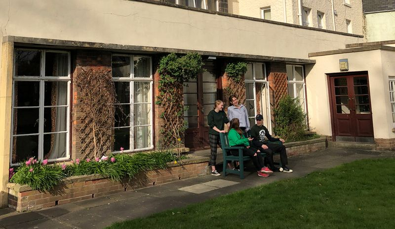 Students sitting on a bench in the back garden of Cuth's buildings on the Bailey.