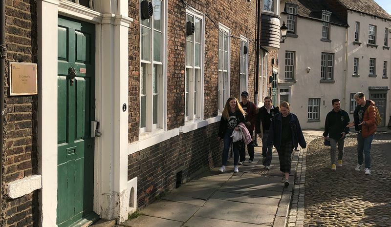View from North to South Bailey with students walking down the cobbled street past historical buildings.