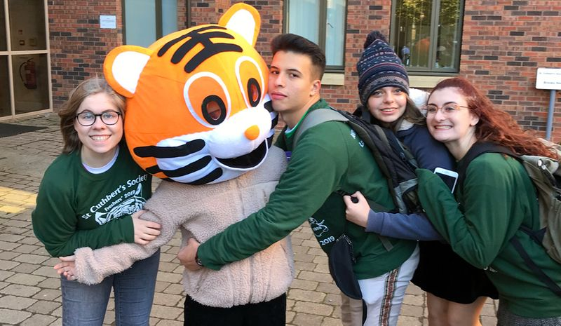 Brooks House, 3 storey student accommodation, modern building with 3 student Fresher's Reps hugging Cuth's Tiger mascot.