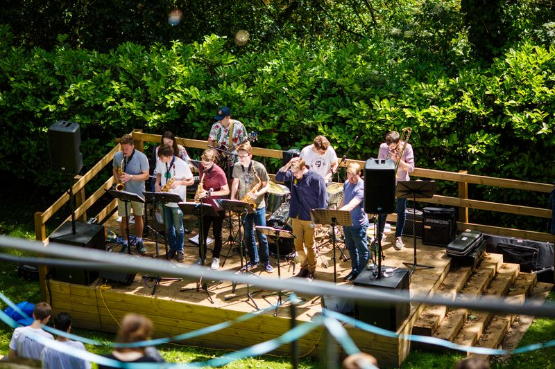 Students playing musical instruments on a wooden outdoor stage
