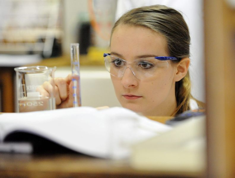 A student with goggles on, conducting an experiment