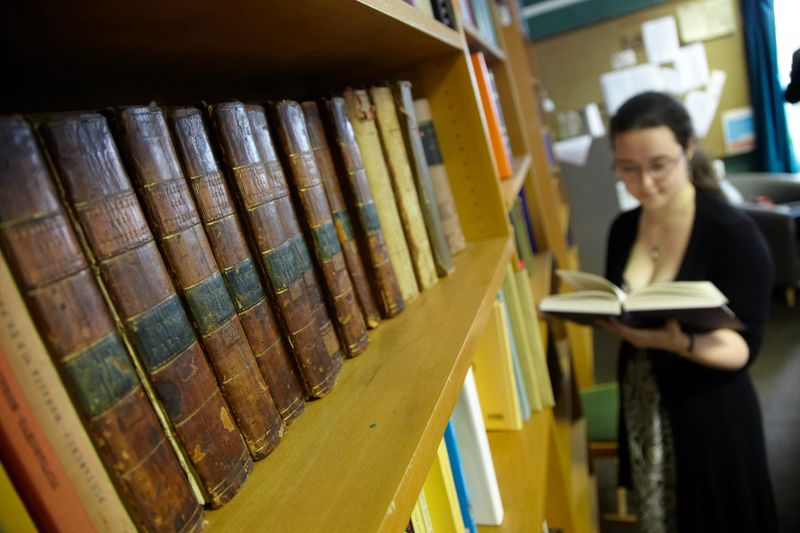 A student reading in the library, by a shelf of historic texts