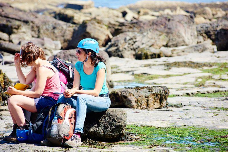Woman sat on rocks wearing helmet