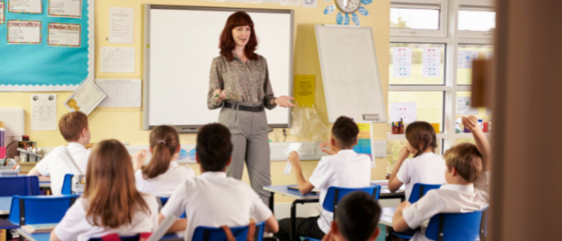 Teacher in classroom in front of whiteboard