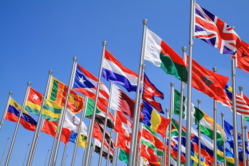 Lots of different flags against a blue sky