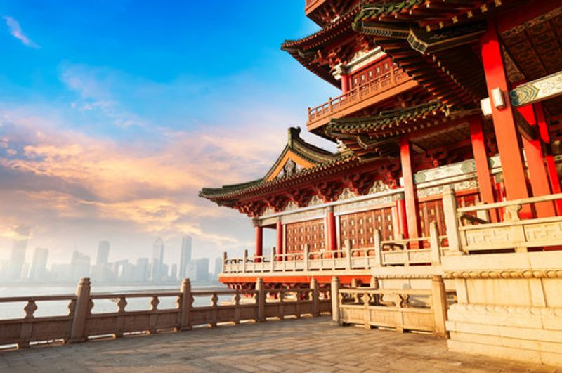 An ancient Chinese building with the modern city skyline in the background