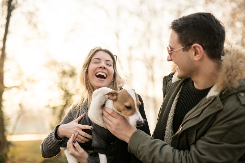 A young couple with a Jack Russell puppy