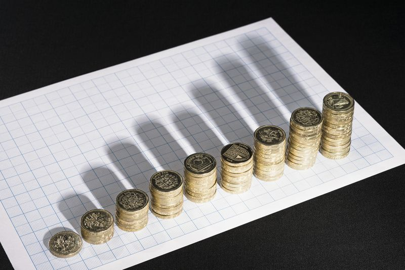 Stacks of coins create shadows across a graph