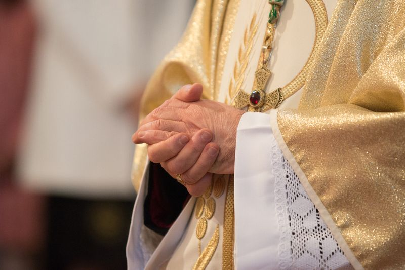 A Catholic priest holding his hands together
