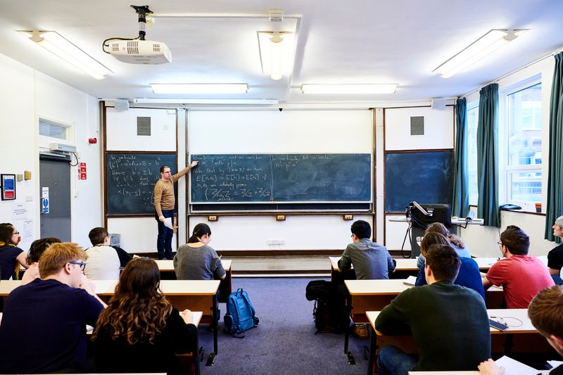 Students sitting in class while the tutor points to the blackboard.