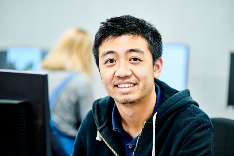 Student sitting in front of a computer, smiling at the camera.