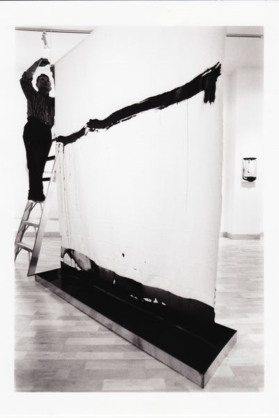 Man on ladder, hanging a painting