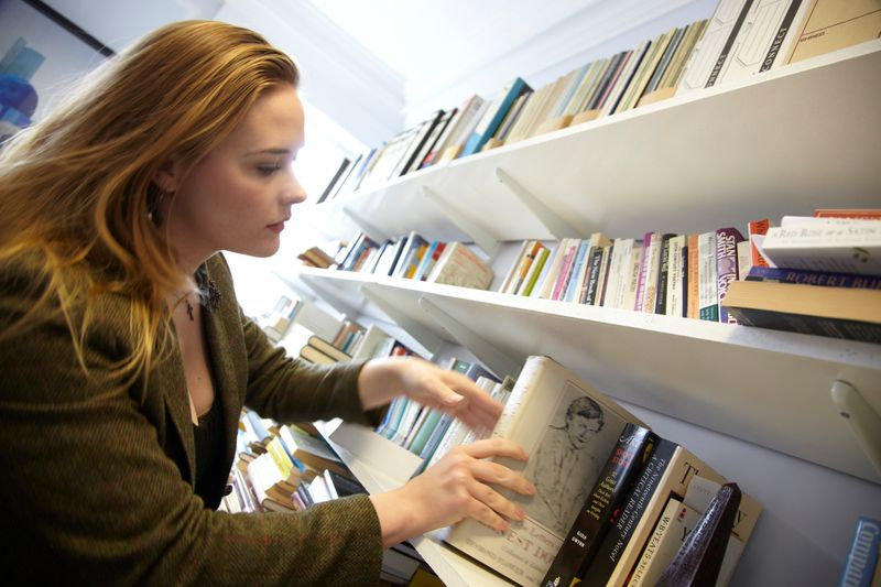 Woman browsing philosophy books on library shelves