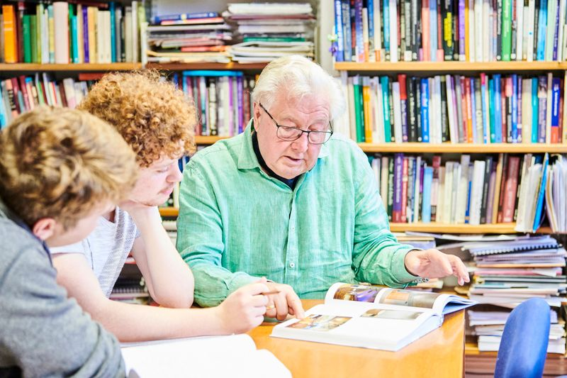 Tutor reading through book with students
