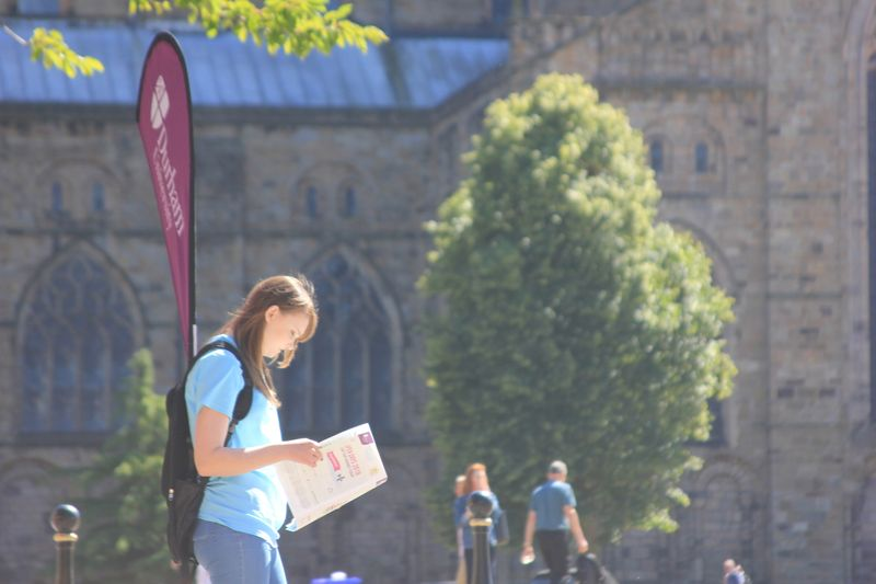 Potential student reading a brochure outside Durham Cathedral