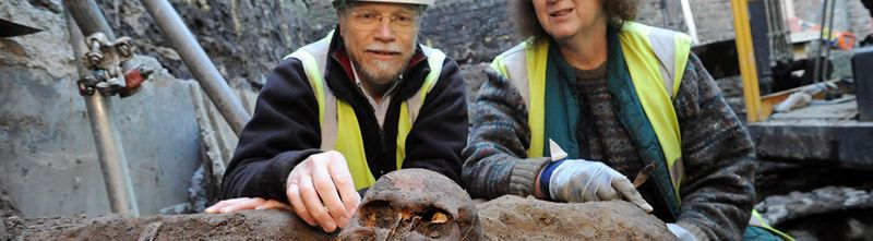 Archaeologist digging up skeleton of Scottish soldiers