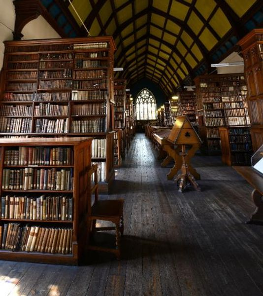 Interior of Ushaw College Library, featuring leather bound books on bookcases
