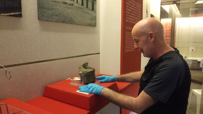 A man wearing purple gloves positions a stone sculpture into a museum display case
