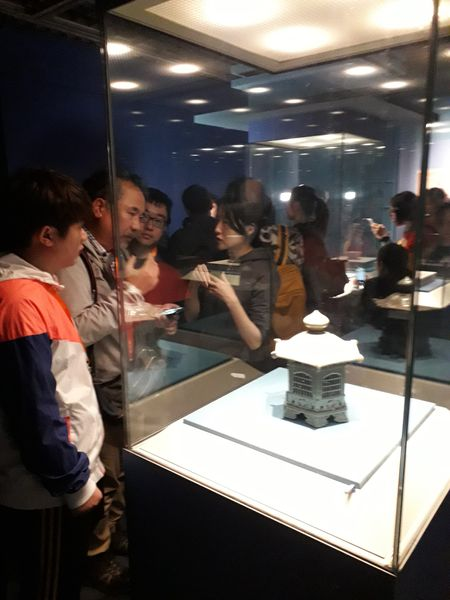Visitors to the Lonquan of the World exhibition look at a lantern on loan from the Oriental Museum