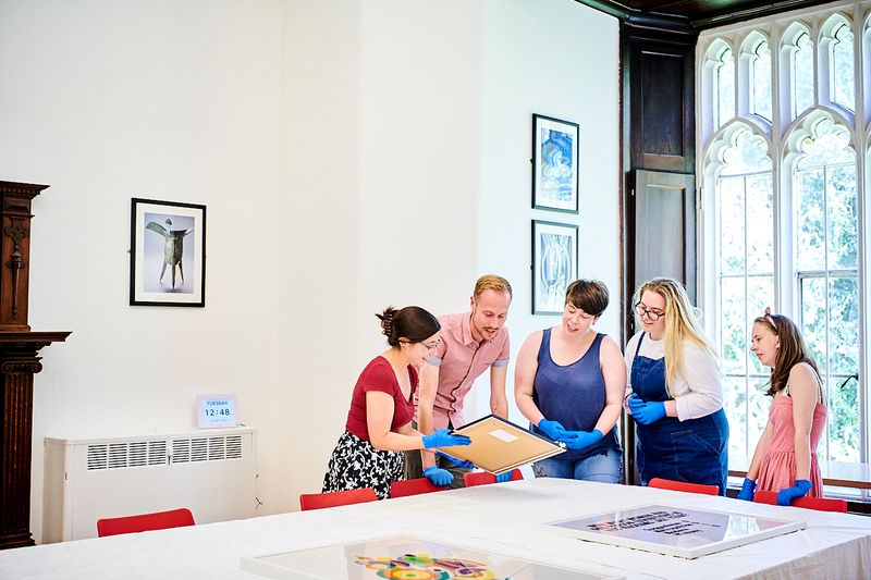 A group of people wearing gloves gather round as a woman shows them a framed picture.