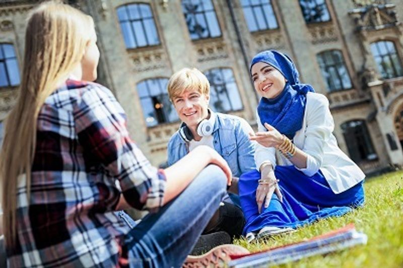 Three students talking while sitting outside