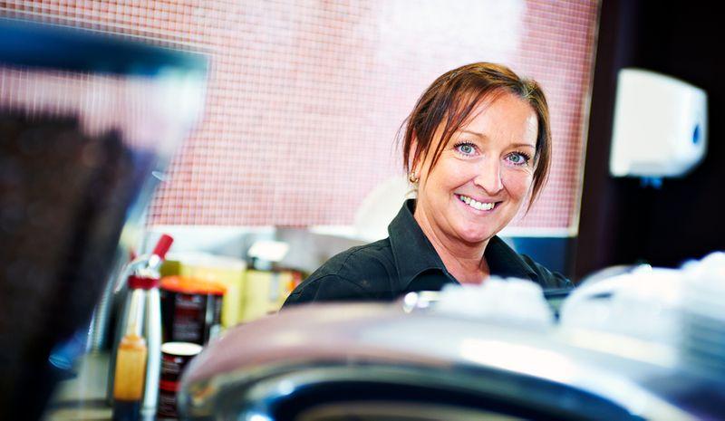 A smiling staff member in Café Aroma, Queens Campus, Stockton
