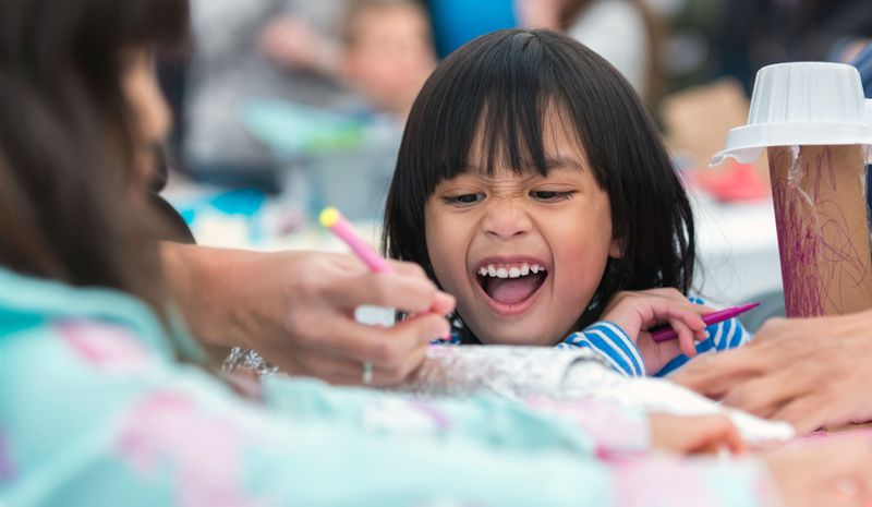 A smiling child at a table with colouring pencils