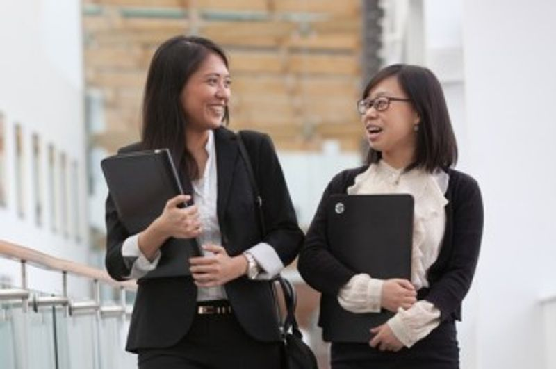 Two businesswomen carrying laptops and talking while walking along a corridor