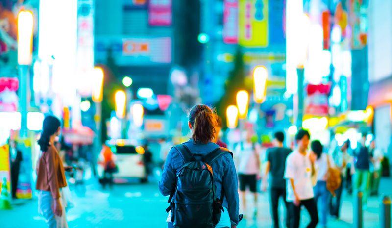 A student walks through a busy neon lit city centre