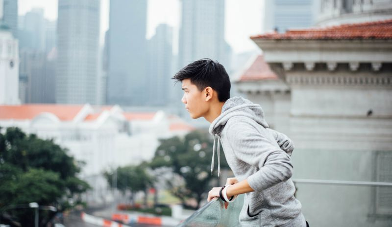 A student on a balcony looks out across a busy city