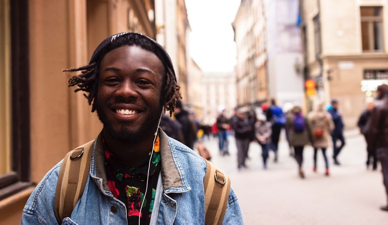 A smiling student walking along a busy street
