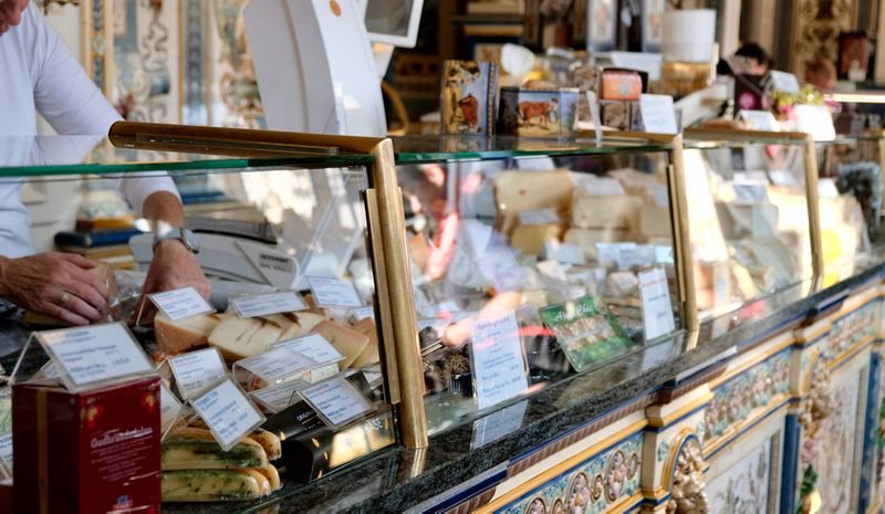 A Dutch delicatessen counter stacked with cheese and smoked meats