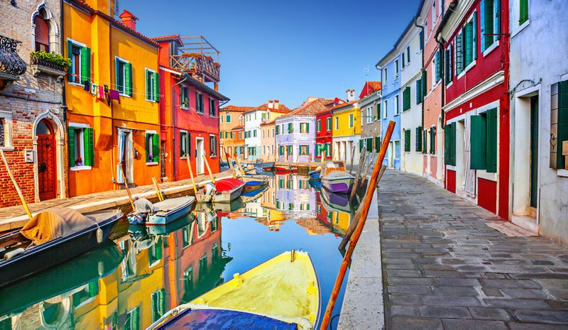 A canal in Burano, Italy lined with colourful buildings