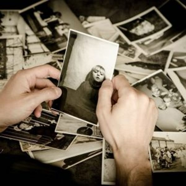 A pair of hands holding a black and white photo