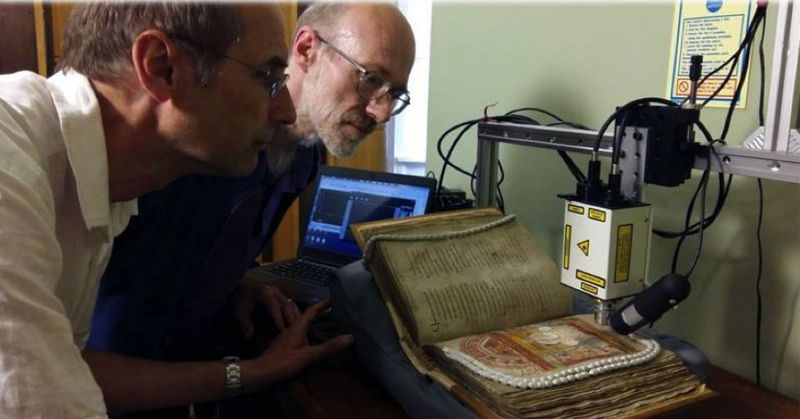Two people examining the St Augustine Gospels at Corpus Christi College, Cambridge