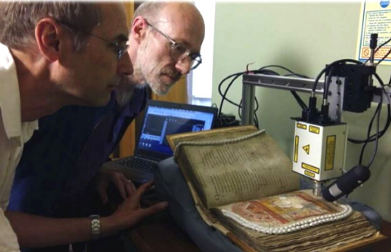 Two researchers looking at a medieval manuscript