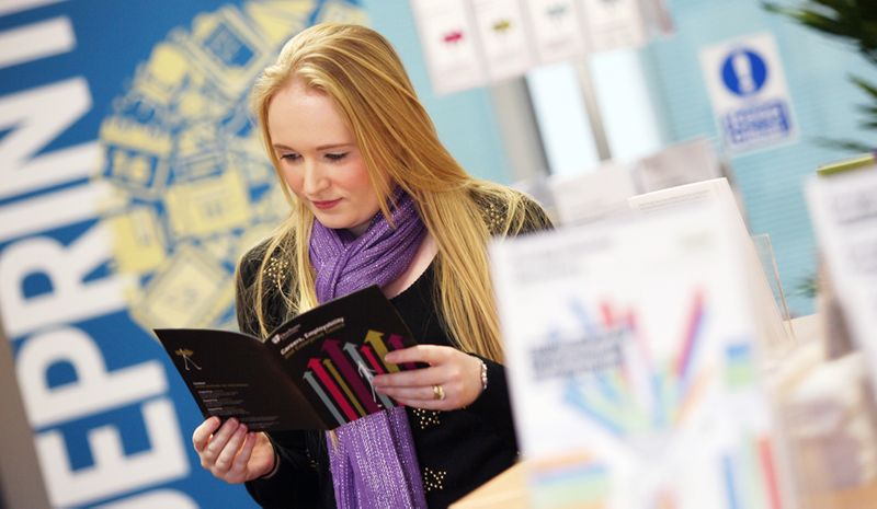 A student browsing various brochures and pamphlets in the Careers and Enterprise Centre