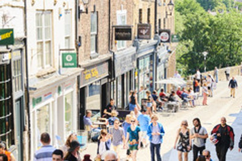 A view of part of Durham city centre busy with people.
