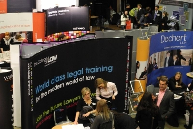 A busy exhibition space full of displays and students