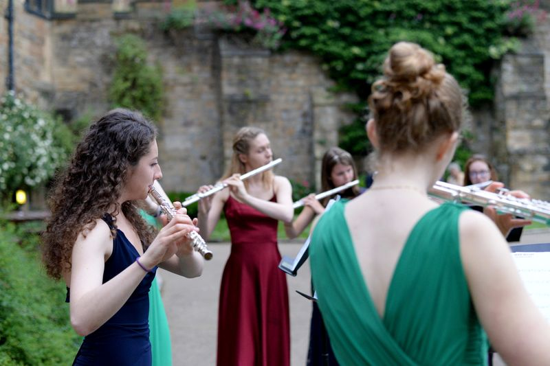 Group of flute players performing outside Durham Castle