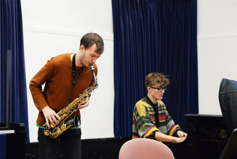 Student playing the saxophone accompanied by pianist