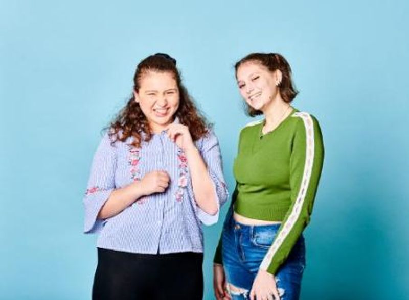 Two students on blue background