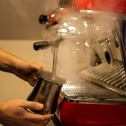 Frothing milk at coffee machine