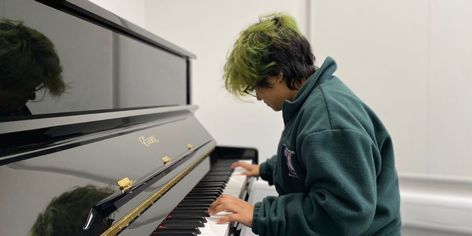 A student playing an upright piano