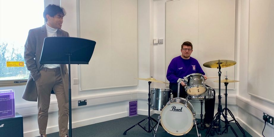 Two students using the music room, one singing and the other playing drums