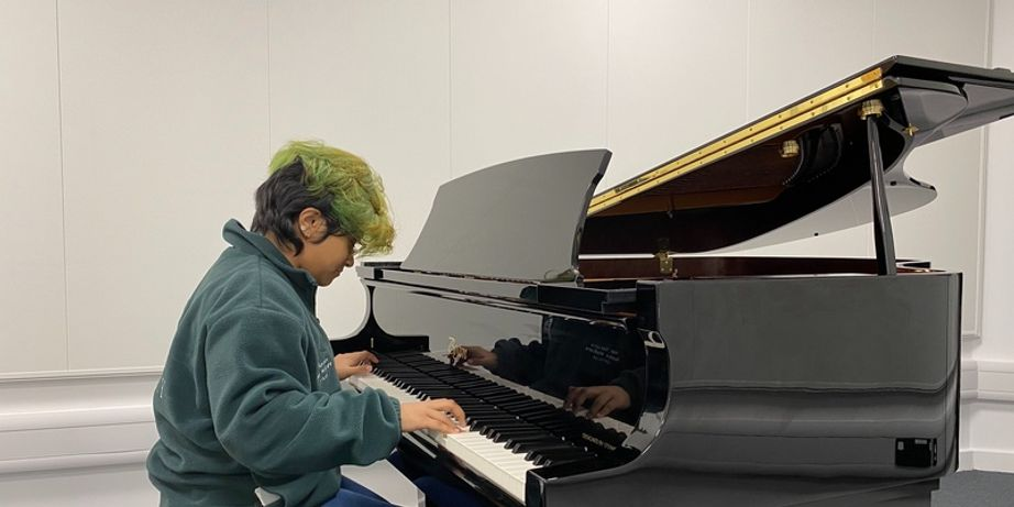 A student playing a baby grand piano